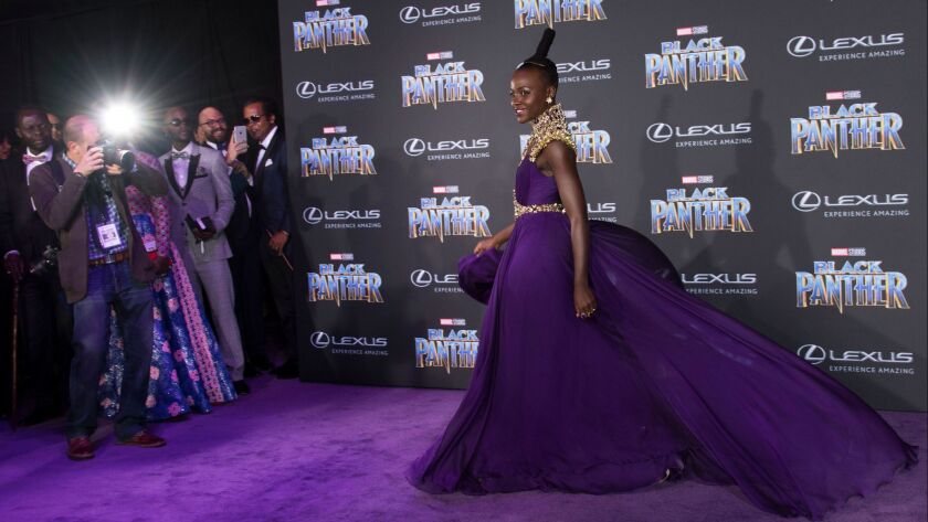 "Wearing a custom-made Atelier Versace gown, Lupita Nyong'o poses on the purple carpet for the premiere of Marvel Studios' ""Black Panther"" on Monday night."