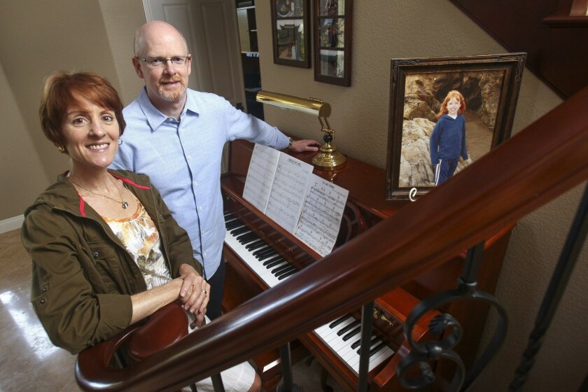 Anita and Jeff Miller of Olivenhain at the piano that their late daughter Ariana, seen in the portrait at right, enjoyed playing before she passed away in 2008. The Millers produce a concert that raises money for the music therapy program that helped Ariana, who had congenital heart disease.