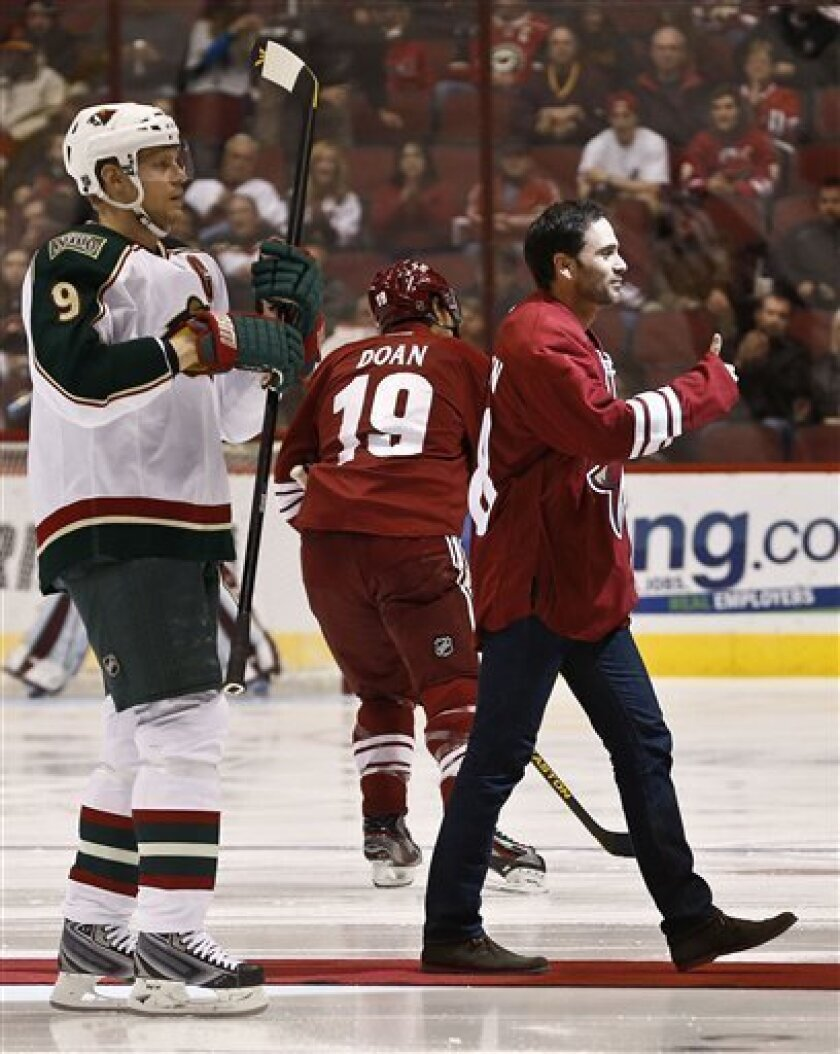 NASCAR driver Jimmie Johnson, right, acknowledges the crowd after dropping the ceremonial first puck to Phoenix Coyotes' Shane Doan (19) and Minnesota Wild's Mikko Koivu (9), of Finland, before an NHL hockey game, Thursday, Feb. 28, 2013, in Glendale, Ariz. (AP Photo/Ross D. Franklin)