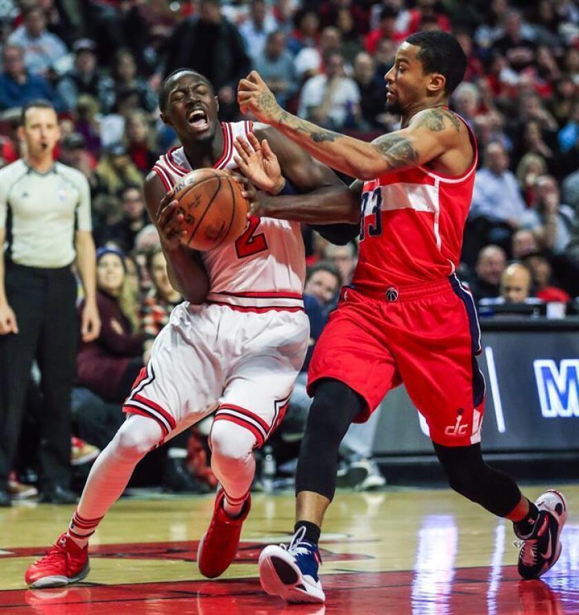 Jerian Grant (i) de Chicago Bulls recibe una falta de Trey Burke (d) de Washington Wizards este miércoles 21 de diciembre de 2016, en un juego de la NBA en United Center en Chicago (EE.UU.). EFE