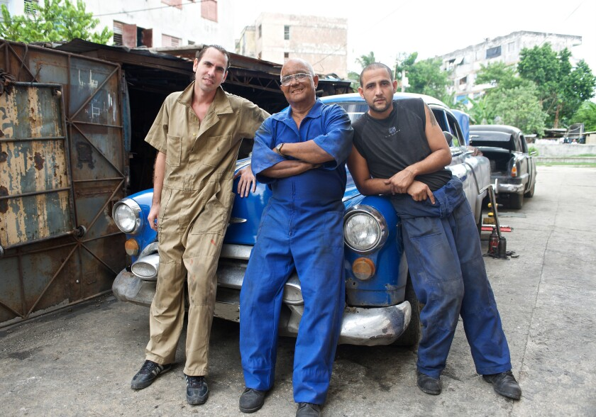 """En esta imagen sin fecha difundida por Discovery en Español, Demetrio Montalvo, en el centro, con sus hijos Michel, a la izquierda, y Hernán, de """"Cuban Chrome"""", una docu-serie sobre autos clásicos estadounidenses en Cuba. La serie se estrena el lunes 13 de julio del 2015."""