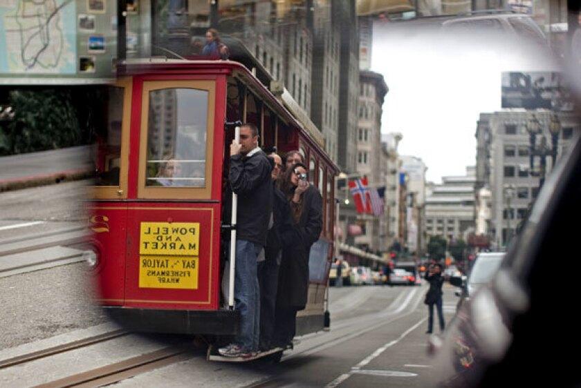 A San Francisco icon, a cable car, moves along Powell, reflected in a car mirror.