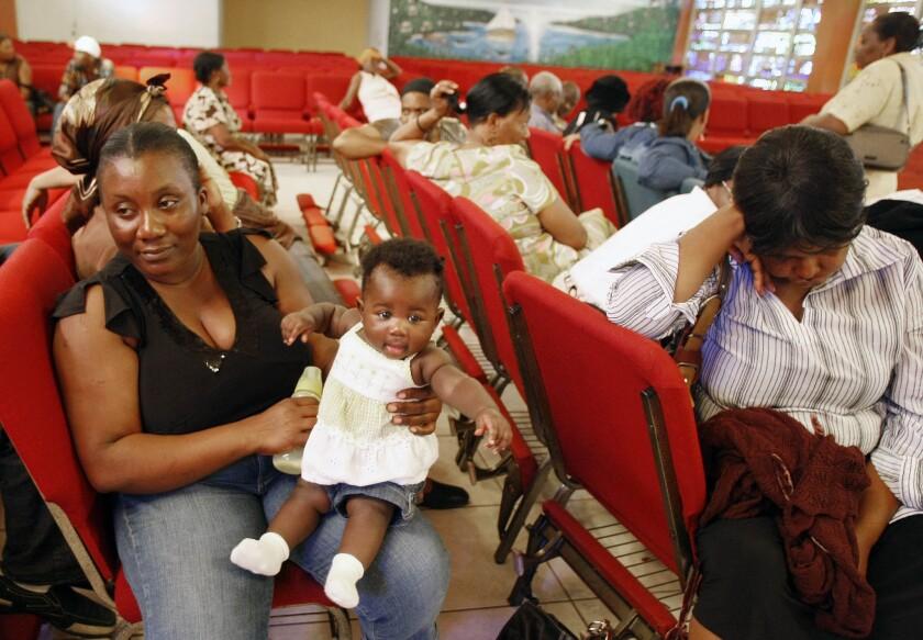 ARCHIVO - En esta foto del 21 de enero del 2010, la haitiana Carole Manigat, espera con su bebé Hadassa Carole Albert por su turno para solicitar estatus migratorio temporal en la iglesia católica Notre Dame d'Haiti en Miami, Florida. El Departamento de Seguridad Nacional de Estados Unidos dijo el jueves, 22 de septiembre del 2016, que está intensificando gestiones para deportar a haitianos, en respuesta a miles de inmigrantes de ese país caribeño que han abrumado los cruces fronterizos desde México en meses recientes. (AP Photo/Alan Diaz)