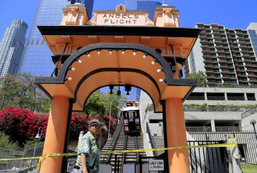 "Pedestrians stroll past Angels Flight after one of the funicular's two rail cars derailed. Six stranded passengers were assisted off ""the world's shortest railway,"" which may remain closed for months."