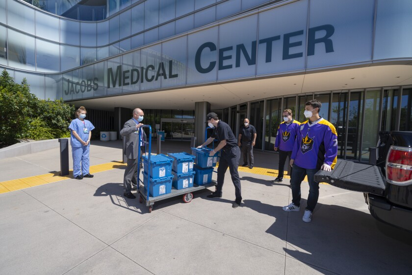 Brad Ouellet (left of cart), director of Supply Chain Management Services at UC San Diego Health, Steve Govett, president of the San Diego Seals lacrosse team (right of cart), UC San Diego Health nurses and Seals players handle a delivery of personal protective equipment.