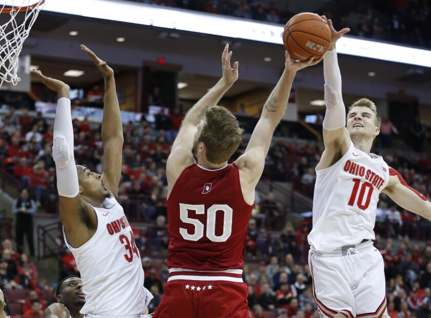 Indiana's Joey Brunk, center, tries to shoot between Ohio State's Kaleb Wesson, left, and Justin Ahrens during the first half of an NCAA college basketball game Saturday, Feb. 1, 2020, in Columbus, Ohio. (AP Photo/Jay LaPrete)