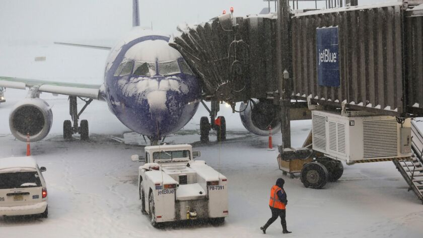 A ground crew member walks past a canceled flight due to a snow storm at the Newark Liberty International Airport on Nov. 15 in Newark, N.J. A storm was expected to blanket the central Midwest on Sunday, grounding hundreds of flights.