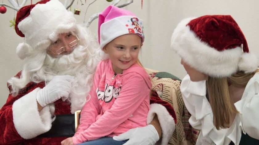 A child gives Santa her wish list at a party at Interfaith Community Services in December in Escondido. The Larry Himmel Neighborhood Foundation underwrote the cost of all the Christmas gifts the children asked Santa for that night.