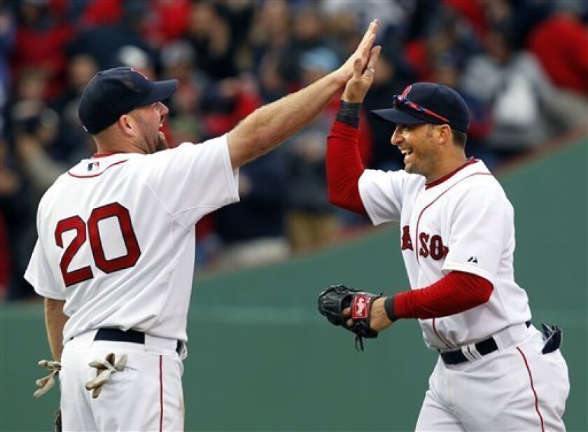 Boston Red Sox third baseman Kevin Youkilis (20) celebrates with shortstop Marco Scutaro after they defeated the New York Yankees in a baseball game at Fenway Park in Boston Friday, April 8, 2011. The Red Sox won 9-6. (AP Photo/Elise Amendola)