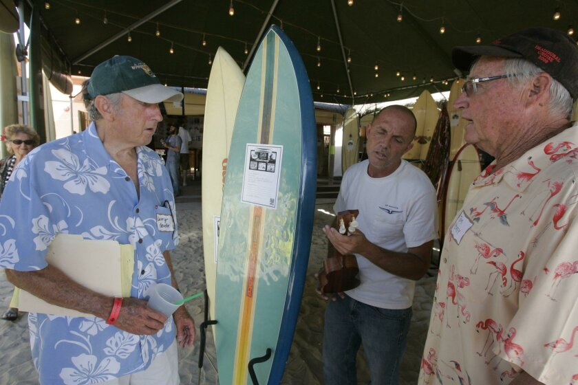 "During the 50th anniversary of Gordon and Smith at the Wave House company co-founder Larry Gordon (left) chatted with longtime San Diego surfer Eric ""Bird"" Huffman. Playing the ukulele, at right, was Tom Morey, longtime surf industry legend and creator of the boogie board. Charlie Neuman"