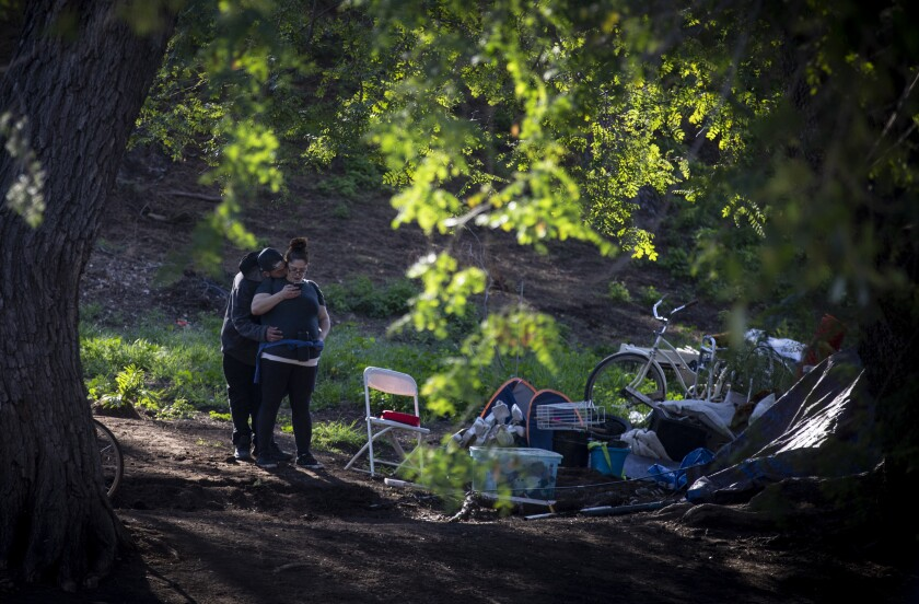 A couple hug at an encampment at Lincoln Park, where many homeless people use mobile showers and hand-washing stations provided by volunteer groups such as Shower of Hope. At a time when frequent hand washing is considered a key to preventing the spread of the novel coronavirus, the closure of many businesses during stay-at-home orders has limited access to soap and water for homeless people.