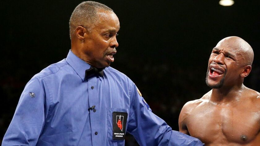 Referee Kenny Bayless hears from Floyd Mayweather Jr. during a fight against Marcos Maidana on Sept. 13, 2014.