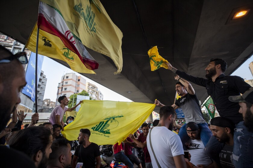 Hezbollah and Amal supporters wave flags as they shout slogans against Israel and the U.S. during a protest Sunday in Beirut.