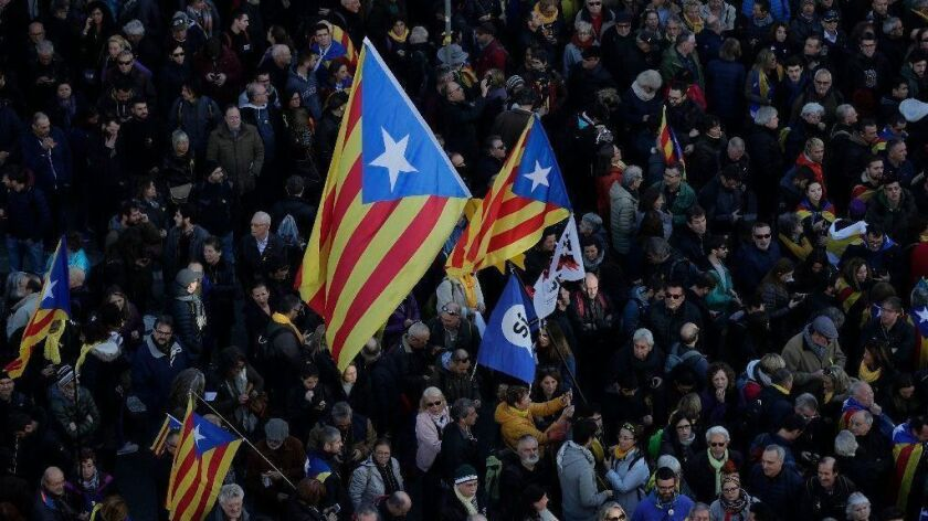 People, some with Catalonia independence flags, protest Spain's Cabinet holding a meeting in Barcelona on Dec. 21, 2018.