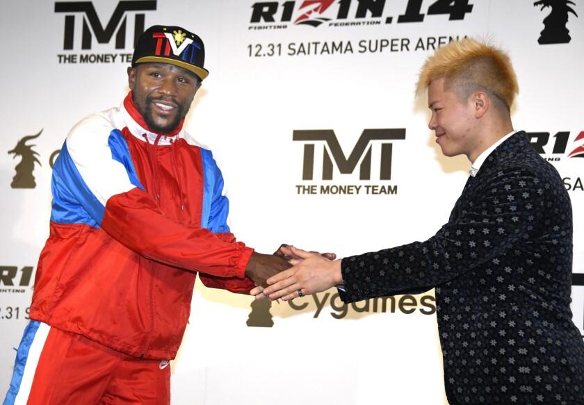 El exboxeador Floyd Mayweather, izquierda, estrecha la mano del japonés experto en kickboxing Tenshin Nasukawa durante una conferencia de prensa en Tokio, el lunes 5 de noviembre de 2018. (Katsuya Miyagawa/Kyodo News via AP) ** Usable by HOY, ELSENT and SD Only **