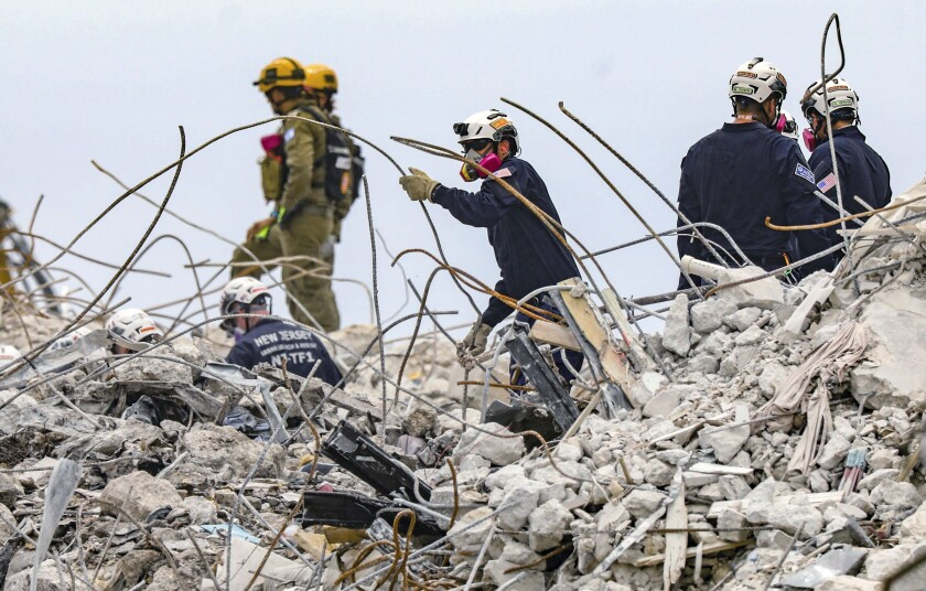 A search and rescue team members dig through the rubble of the Champlain Towers South condo, Wednesday, July 7, 2021. (Al Diaz/Miami Herald via AP)