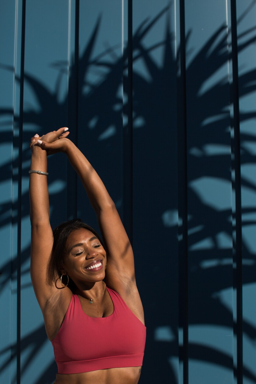 Danielle Richardson, an optometrist turned yoga instructor, stretches in the sun.