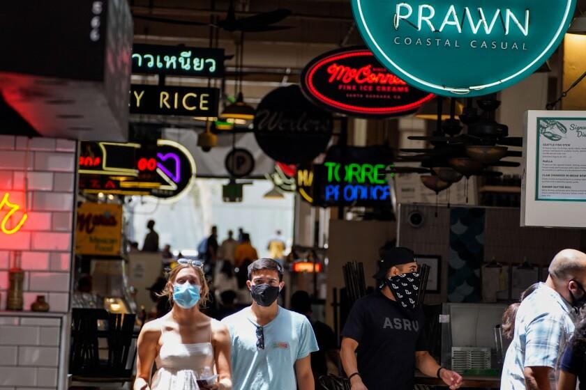 People wearing masks walk in downtown Los Angeles in June 2020.