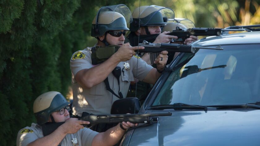 Sheriff's deputies crouch behind a minivan during a search for the assailants in the December 2015 mass shooting in San Bernardino.