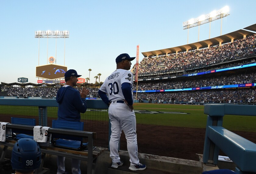Dodgers manager Dave Roberts looks on from the dugout before Game 5 of a National League Division Series game against the Nationals on Oct. 9 at Dodger Stadium.