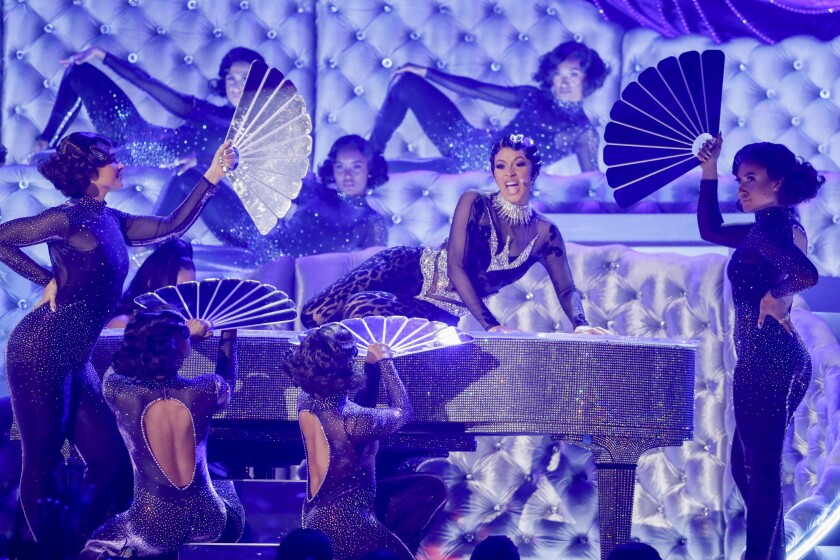 Cardi B performs at the 61st Grammy Awards, on top of a piano and surrounded by dancers.