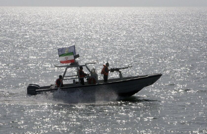 FILE- In this Monday, July 2, 2012 file photo, an Iranian Revolutionary Guard speedboat escorts a passenger ship, unseen, near the spot where an Iranian airliner was shot down by a U.S. warship 24 years ago killing 290 passengers. The U.S. Navy again has accused Iranian patrol boats of harassing an