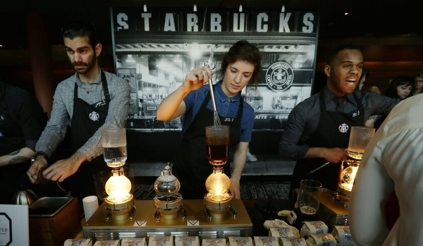 """FILE - In this Wednesday, March 23, 2016, file photo, Starbucks workers prepare coffee using siphon vacuum coffee makers at a station in the lobby of the coffee company's annual shareholders meeting in Seattle. In July 2016, some Starbucks customers gave their names to baristas as """"Black Lives Matter"""" in an effort to help spread awareness of the movement. (AP Photo/Ted S. Warren, File)"""
