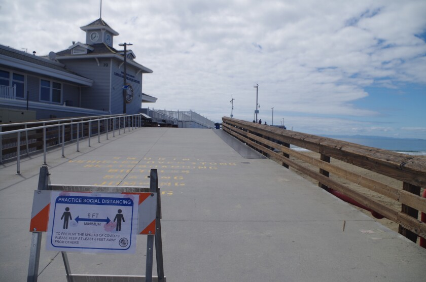 Signs remind visitors to Newport Pier to keep their distance to prevent spread of the coronavirus.