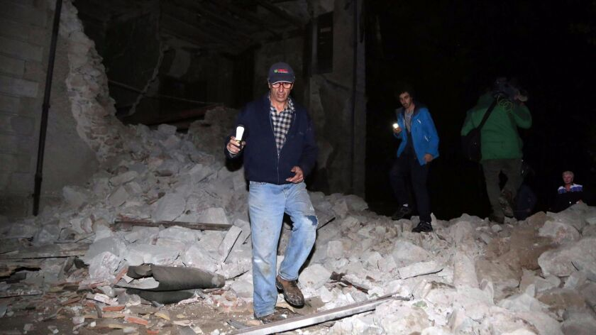 Residents walk past rubble in the village of Visso, in central Italy, after an earthquake on Wednesday.