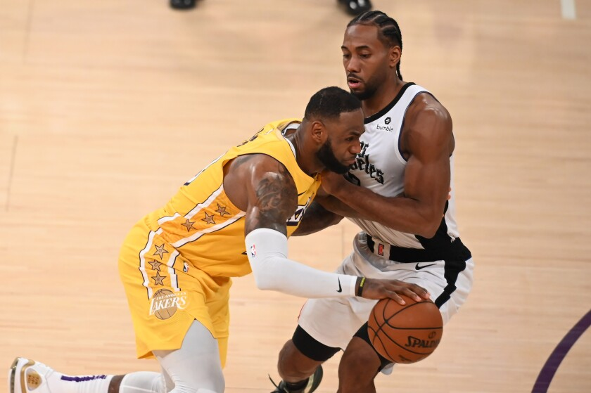 The Lakers' LeBron James drives on the Clippers' Kawhi Leonard on Dec. 25, 2019, at Staples Center.