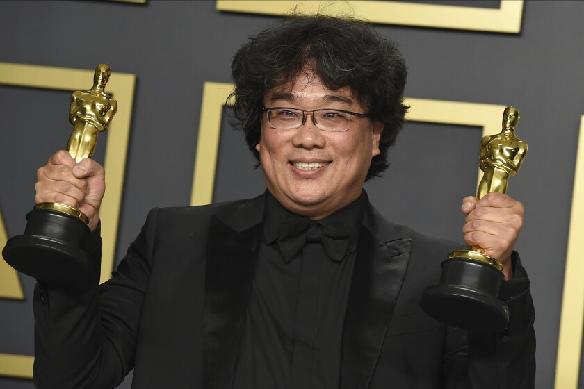 """Bong Joon Ho poses in the press room with the awards for best director for """"Parasite"""" and for best international feature film for """"Parasite"""" from South Korea at the Oscars on Sunday, Feb. 9, 2020, at the Dolby Theatre in Los Angeles. (Photo by Jordan Strauss/Invision/AP)"""