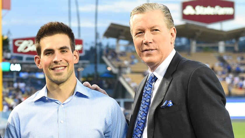 Dodgers broadcasters Joe Davis and Orel Hersheiser pose on the field together before a game against the San Francisco Giants in September 2016.