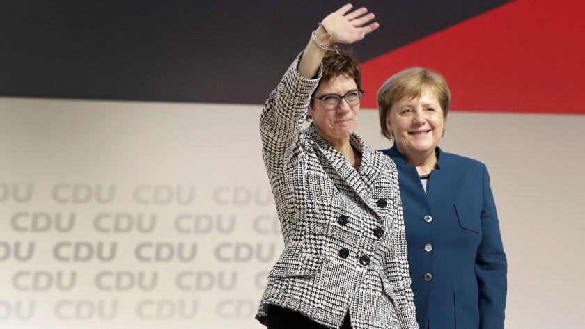 Newly elected CDU chairwoman Annegret Kramp-Karrenbauer, left, is flanked by German Chancellor Angel