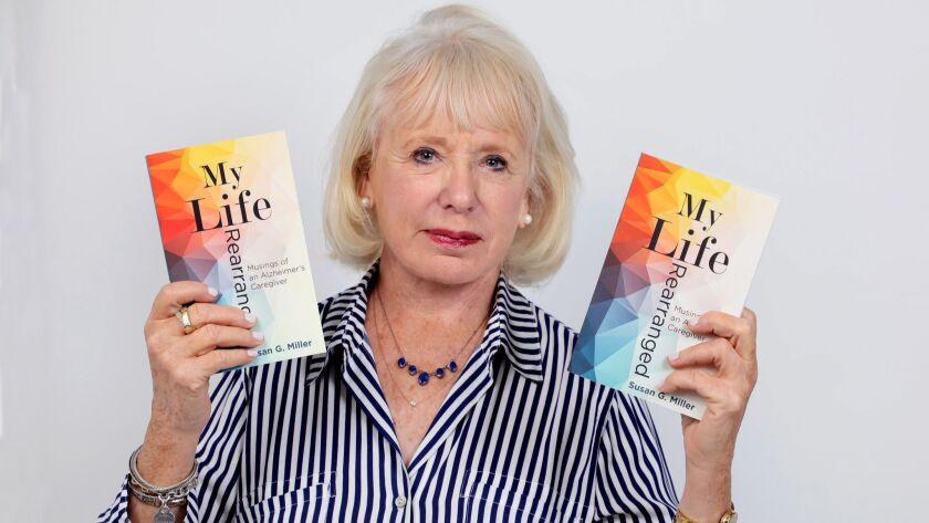 Portrait of author Susan Miller, with copies of her book, My Life Rearranged.