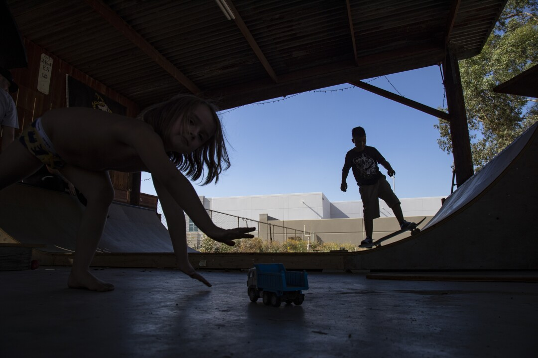 Aiden Kuhl, 4, and Braiden Roberts, 10, play in a Fontana yard