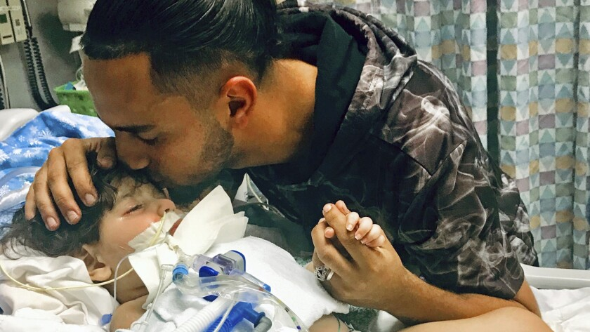 Ali Hassan with his dying 2-year-old son Abdullah in an Oakland hospital in a photo released Dec. 17.