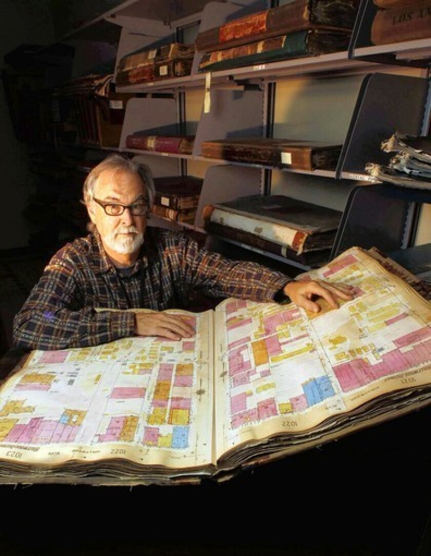 Glen Creason, map librarian at the Los Angeles Central Library, pulls out one of the large, heavy volumes of Sanborn maps — detailed drawings of each block of the city prepared for insurance purposes that are troves of information about old Los Angeles.