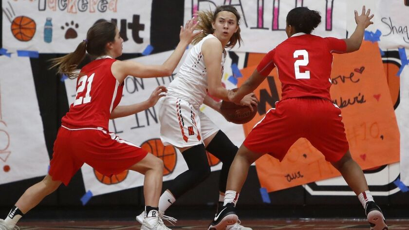 Los Alamitos High's Molly Clarke (21) and Asia Avinger (2) trap and force a turnover by Huntington B