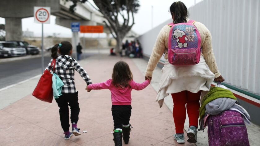 A migrant mother seeking asylum in the U.S. walks with her two daughters and their belongings on their way to the port of entry in Tijuana on June 21.