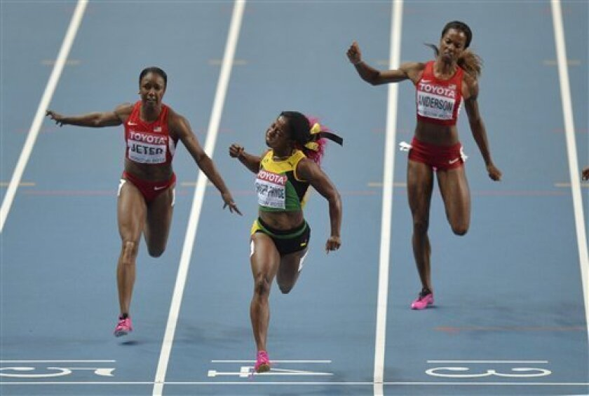 Jamaica's Shelly-Ann Fraser-Pryce, center, crosses the finish line to win gold ahead of United States' Carmelita Jeter, left, and United States' Alexandria Anderson in the women's 100-meter final at the World Athletics Championships in the Luzhniki stadium in Moscow, Russia, Monday, Aug. 12, 2013. (AP Photo/Martin Meissner) .