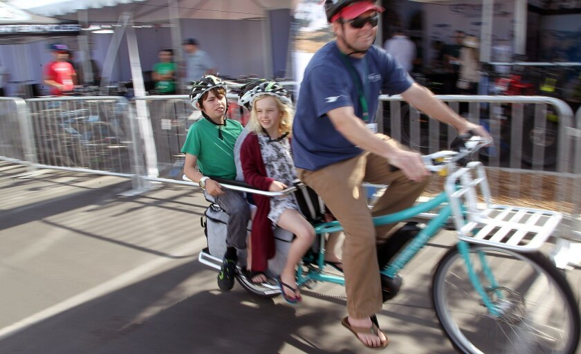  David Tillson, who lives in nearby Point Loma, pedals around on an electric cargo bike with children Paige, 8, Shane, 9, and Cole, 12, at the San Diego Electric Bike Expo.