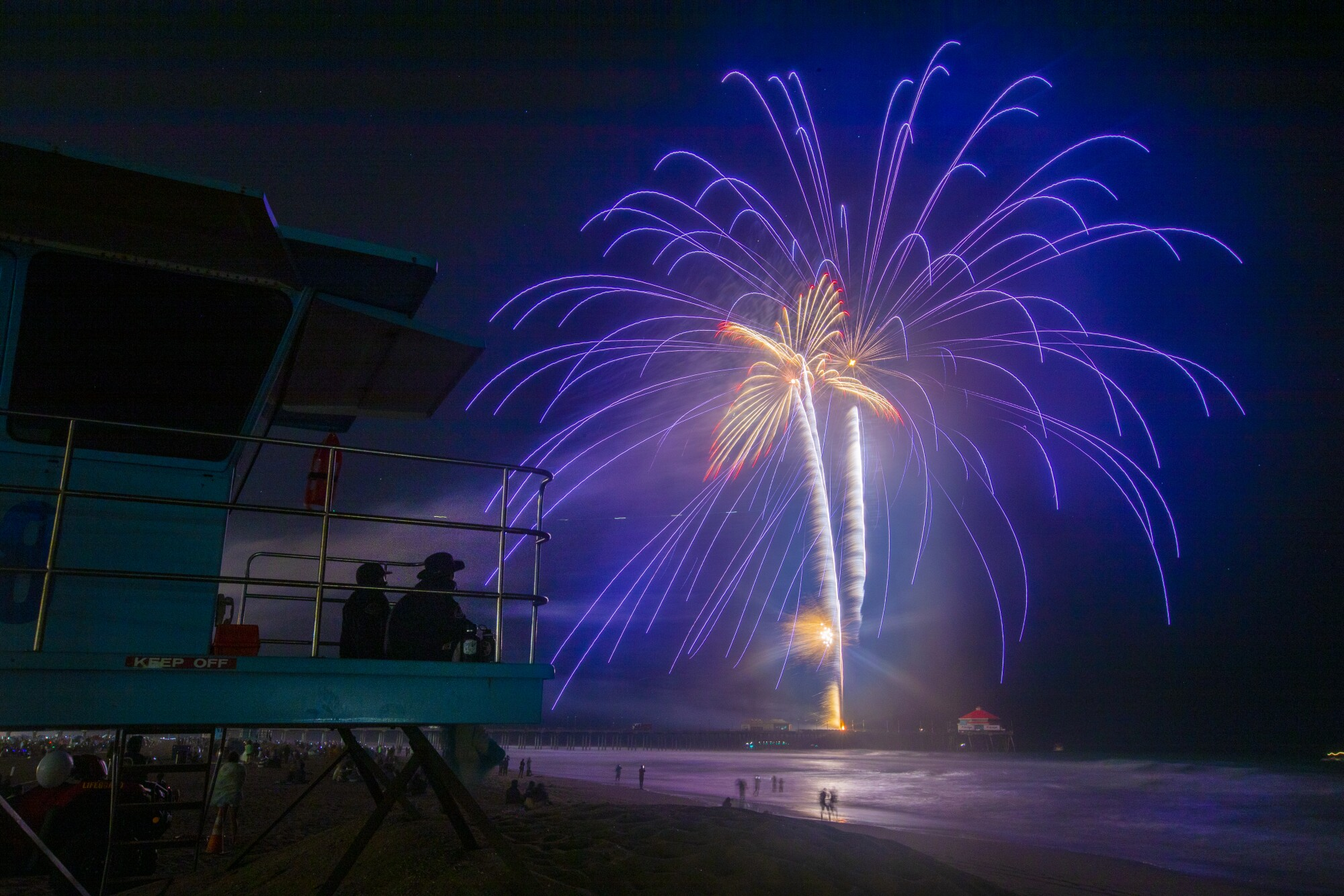 Lifeguards in a tower watch a shower of purple and yellow sparks from fireworks