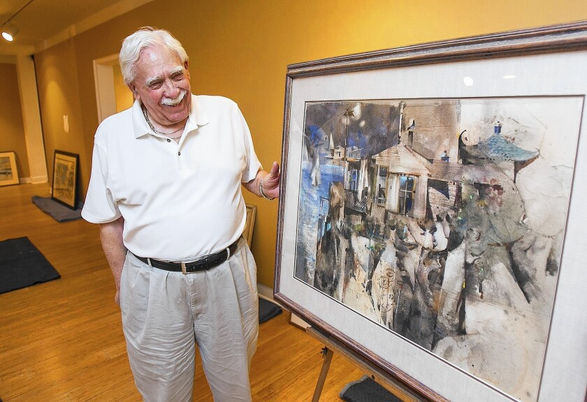 """Gene Crain, a collector who provided many of the pieces for the Rex Brandt exhibit """"In Praise of Sunshine,"""" looks at a piece he owns, """"Morning Rocky Point,"""" at the Laguna Art Museum on Wednesday."""
