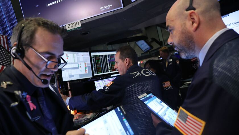 The Dow Jones industrial average fell 0.3% to 26,341.02 on Monday. Above, traders work on the floor of the New York Stock Exchange.