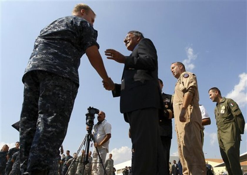Defense Secretary Leon Panetta greets personnel and hands out coins from the office of the Secretary of Defense while visiting the Sigonella Naval Air Station and NATO regional operations center, Friday, Oct. 7, 2011 in Sigonella, Italy. Panetta met with pilots and other personnel who have been in involved with operations over Libya while visiting the base. He is scheduled to travel to Sicily later in the day to visit with U.S. pilots involved in operations over Libya. (AP Photo/Win McNamee, Pool)