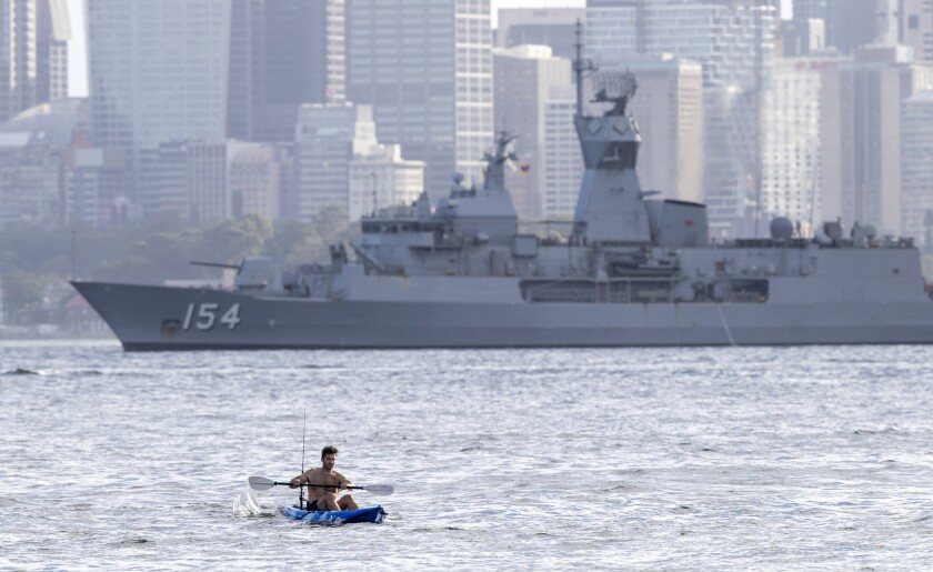 A man paddles his kayak past the HMAS Arunta, an Anzac-class frigate of the Royal Australian Navy, in Sydney harbor, Australia, Tuesday, April 6, 2021. New Zealand announced the start date for a long-anticipated travel bubble between Australia and New Zealand that will allow people to travel between the two countries without going through quarantine, allowing families to reunite and giving a big boost to the struggling tourism industry will begin April 19. (AP Photo/Mark Baker)