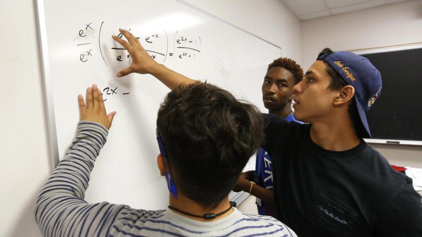Alejandro Fernández (der.), asistente del profesor, ayuda a Carlos Rivas (izq.) y a David-Earl Russell, ambos de 17 años, con una ecuación de precálculo, como parte de la preparación universitaria de USC (Mel Melcon/Los Angeles Times).
