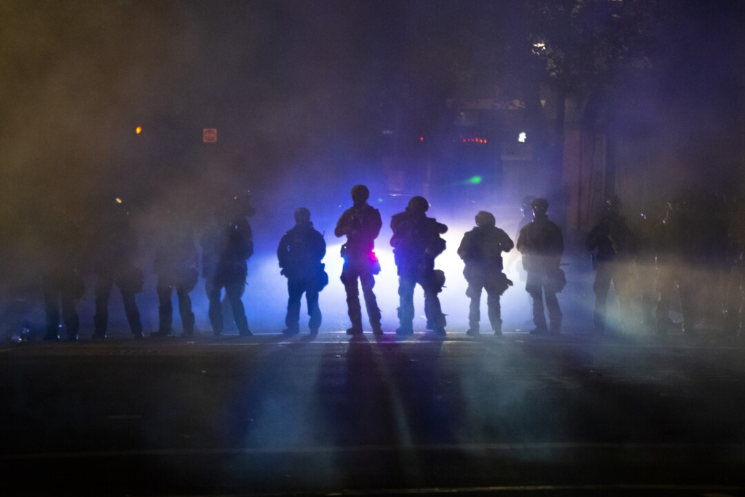 Federal officers walk through tear gas while dispersing a crowd at Mark O. Hatfield U.S. Courthouse in Portland, Ore.