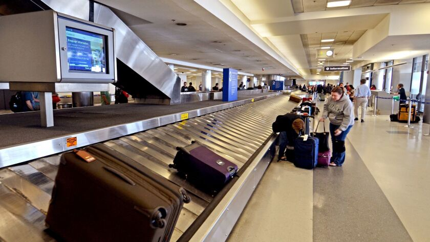 """Passengers pick up their luggage at Los Angeles International Airport. The National Economic Council issued a report that criticized """"hidden fees"""" charged by airlines and other businesses."""