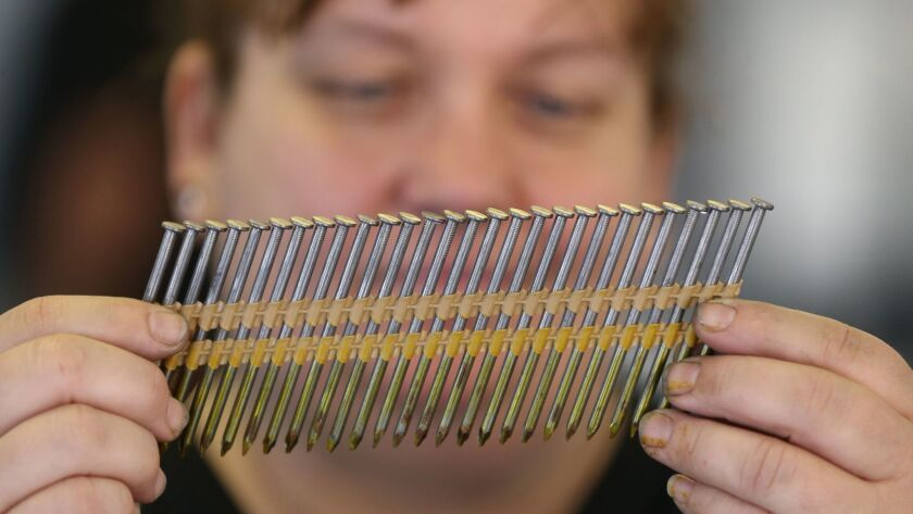 Diane Brogdon, a machine operator at the Mid Continent Nail Corp., looks at a set of nails that fit into a nail gun at the company production factory in Poplar Bluff, Mo.